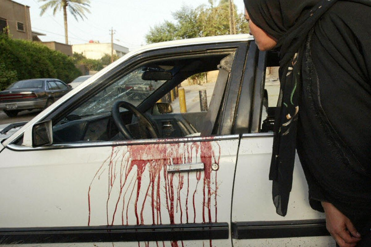 Witnesses look into a car after Blackwater agents killed 17 Iraqis in Nisour Square in 2007.