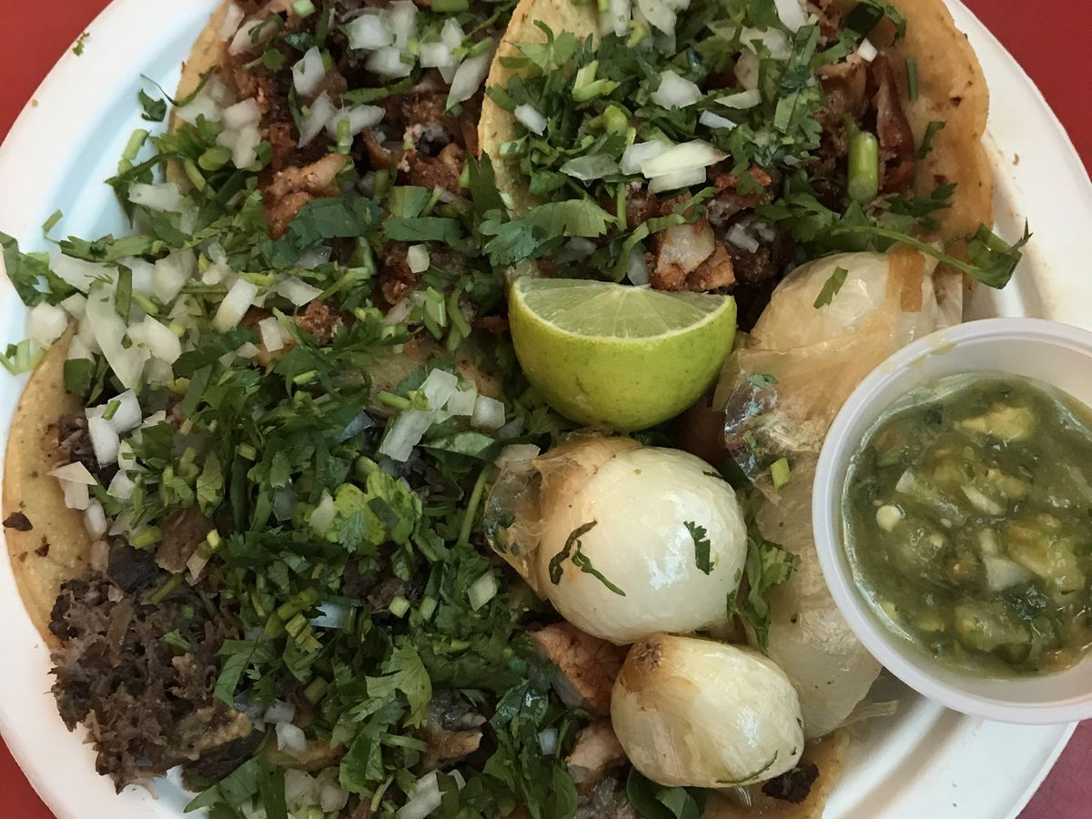 From above, tacos piled on top of one another on a paper plate overflow with chopped meat, diced onions and herbs, alongside a plastic cup of salsa and lime wedge