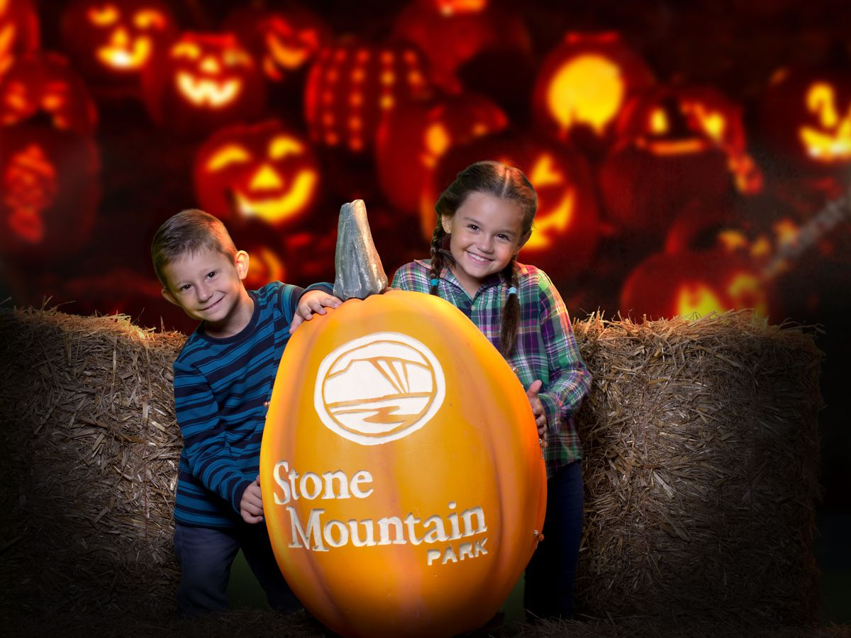 Two kids sitting with a large orange pumpkin with a backdrop of lit jack-o-lanterns.