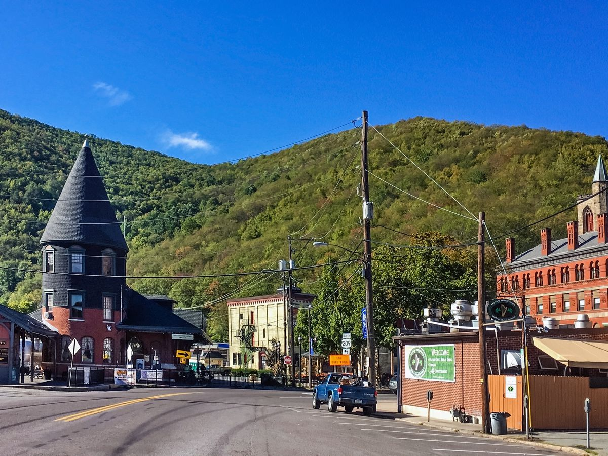 A street in the town of Jim Thorpe, Pennsylvania. The street is lined with buildings and shops. In the distance are mountains.