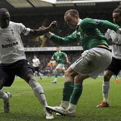 Tottenham Hotspur's Ledley King, left, tries to stop a shot from Norwich City's Aaron Wilbraham during their English Premier League soccer match at White Hart Lane stadium, in London, Monday, April 9, 2012.