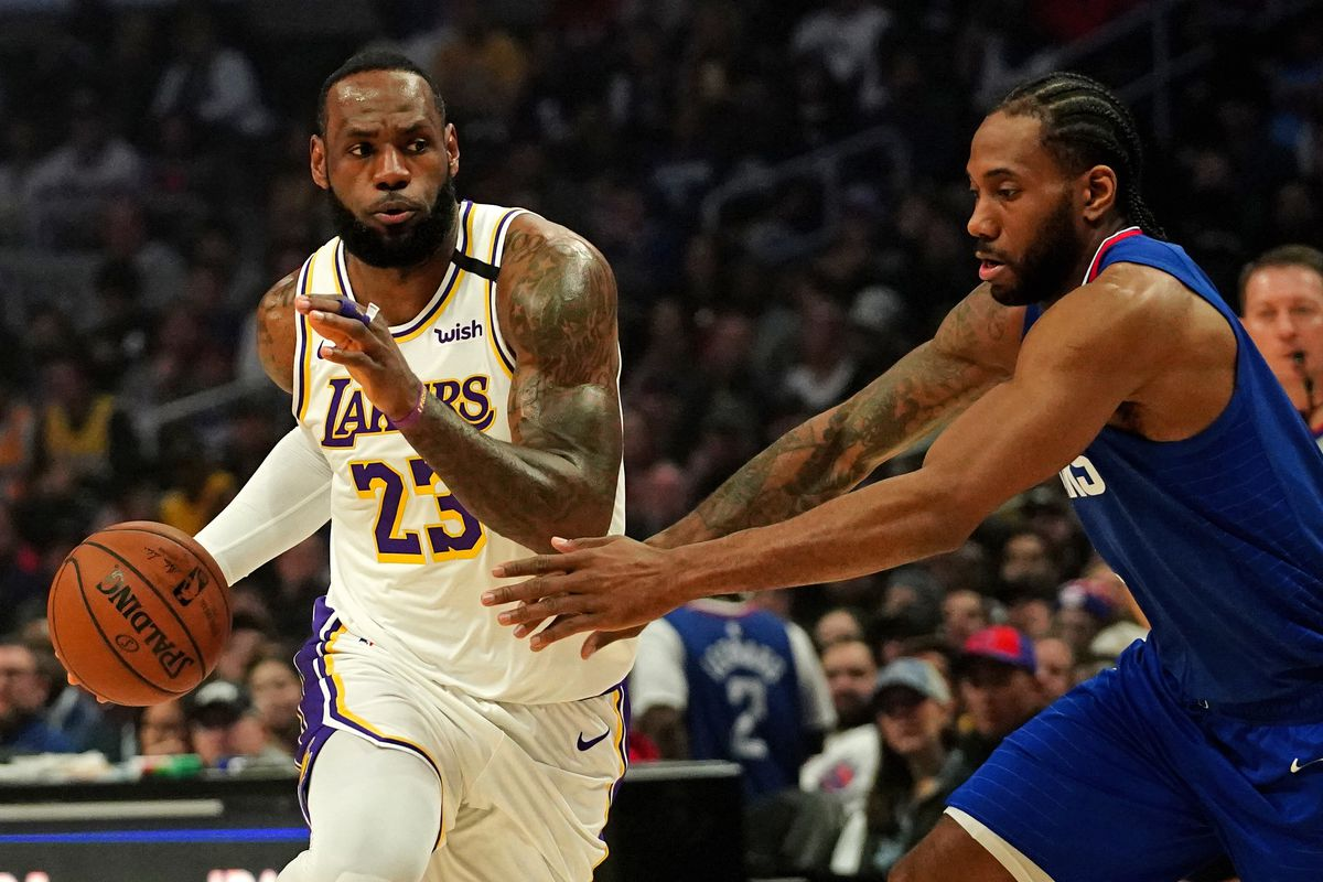 Los Angeles Lakers forward LeBron James dribbles the ball as LA Clippers forward Kawhi Leonard defends in the first half at Staples Center.