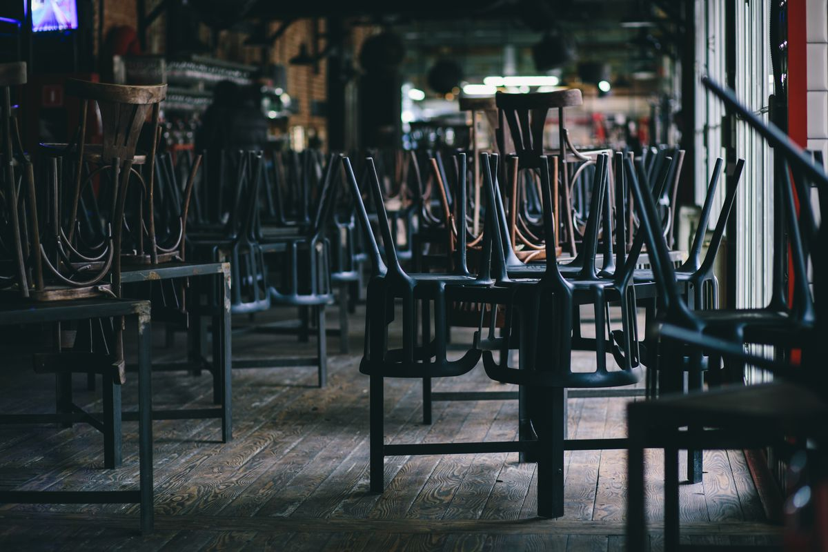 Chairs turned over on tables in a darkened dining room