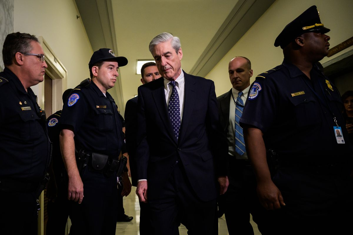 Robert Mueller walks down a hallway lined with uniformed police officers.
