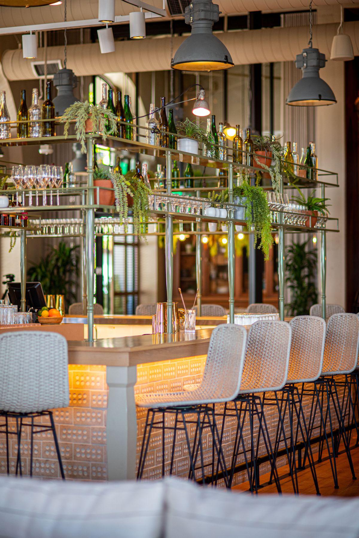 Lights glow under a bar inside of a new restaurant.