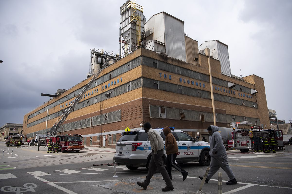 Employees with Bloomer Chocolate Company walk by as fire fighters clean up the scene where a fire broke out at Bloomer Chocolate Company in the 600 block of West Kinzie, Tuesday, April 14, 2020.