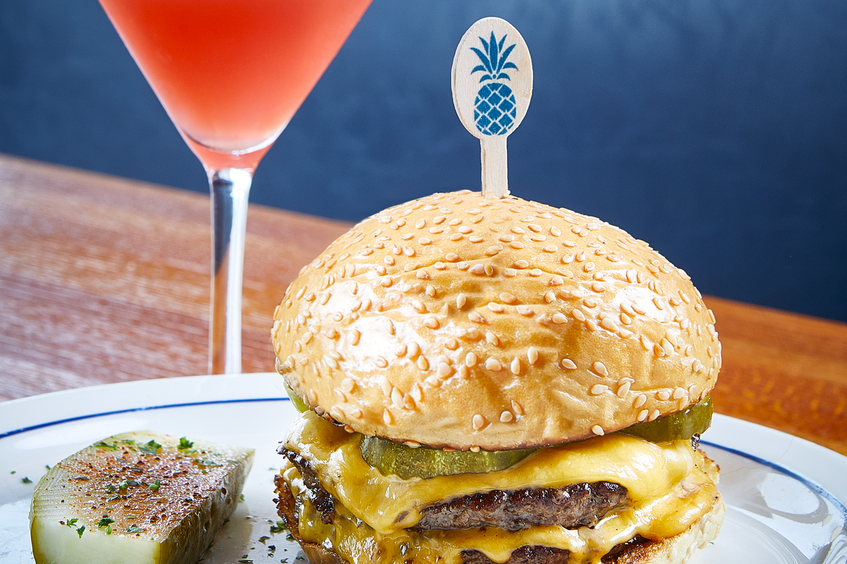 A burger sitting on a plate, topped with cheese and pickles. A half pickle sits next to the burger, with a red cocktail in a martini glass behind it