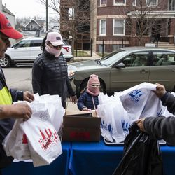 Dulce Herrera, 27, and her 4-year-old daughter Mia Nicole Manzanares receive three days of free breakfast and lunch meals from lunchroom workers at William P. Nixon Elementary School, 2121 N. Keeler Ave., Thursday morning, March 19, 2020.