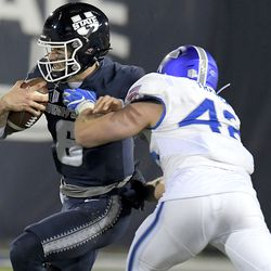 Utah State quarterback Andrew Peasley (6) is tackled by Air Force linebacker Will Trawick (42) during the first half of an NCAA college football game Thursday, Dec. 3, 2020, in Logan, Utah.