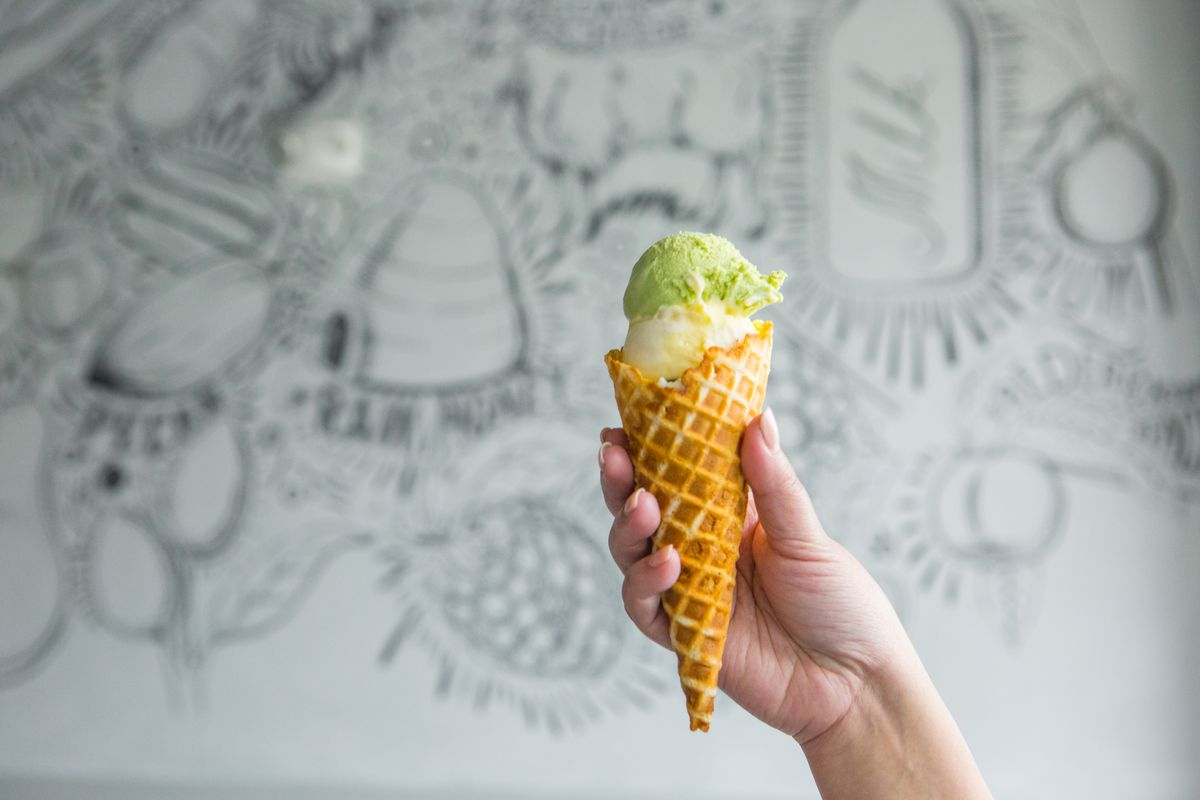 An ice cream cone of a green scoop on top of a white scoop held in front of a black and white mural