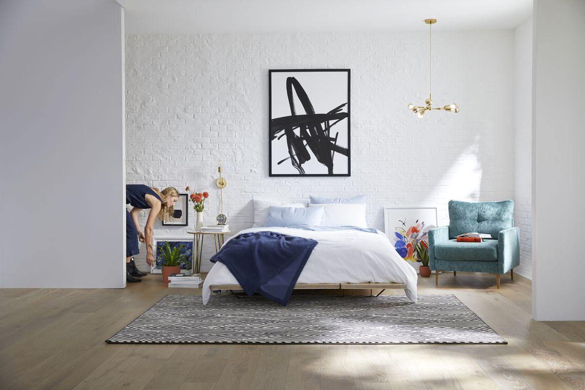 Bedroom with a bed on a beige rug, a teal armchair, and black and white art piece on the wall.