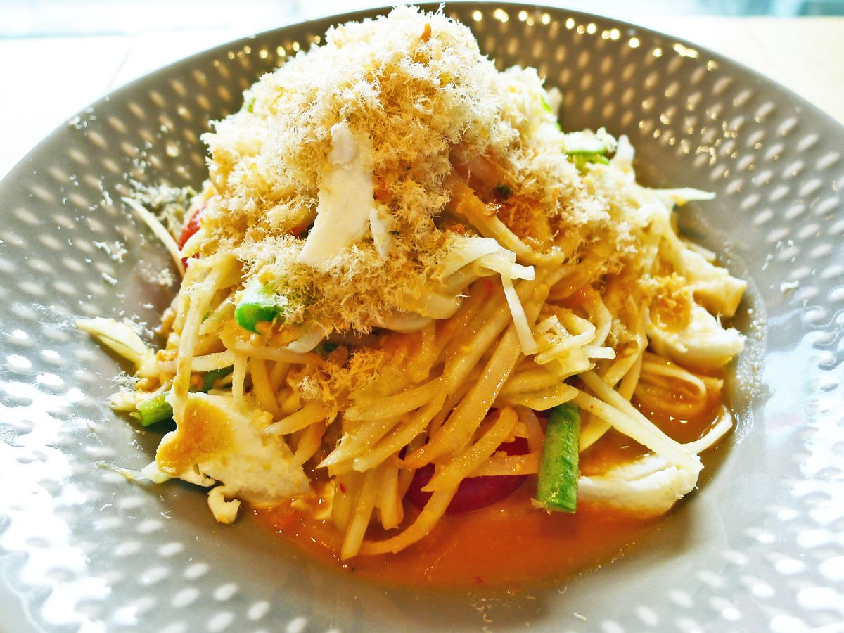 A shredded green papaya salad heaped on the plate in an orangish dressing.
