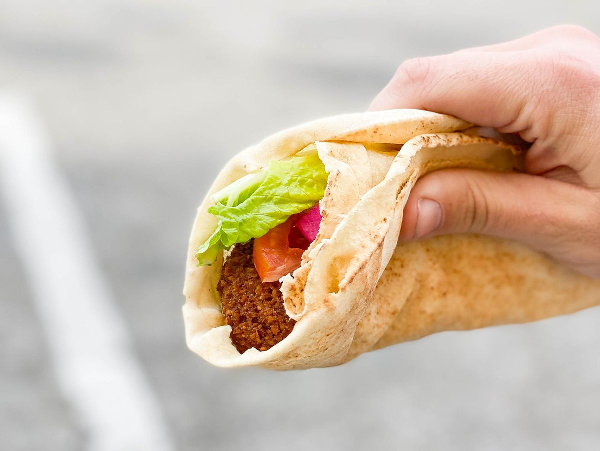 The end of a falafel sandwich, held in hand.