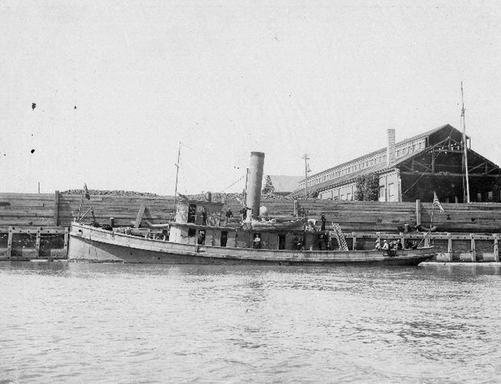 A black and white photo of a floundering boat docked near a damaged building.