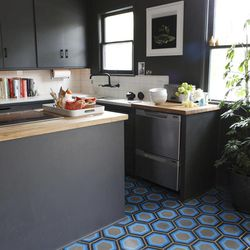 This undated publicity image provided by Kismet Tile shows Hexagon #8 tile in shades of blue and gray in a kitchen floor.