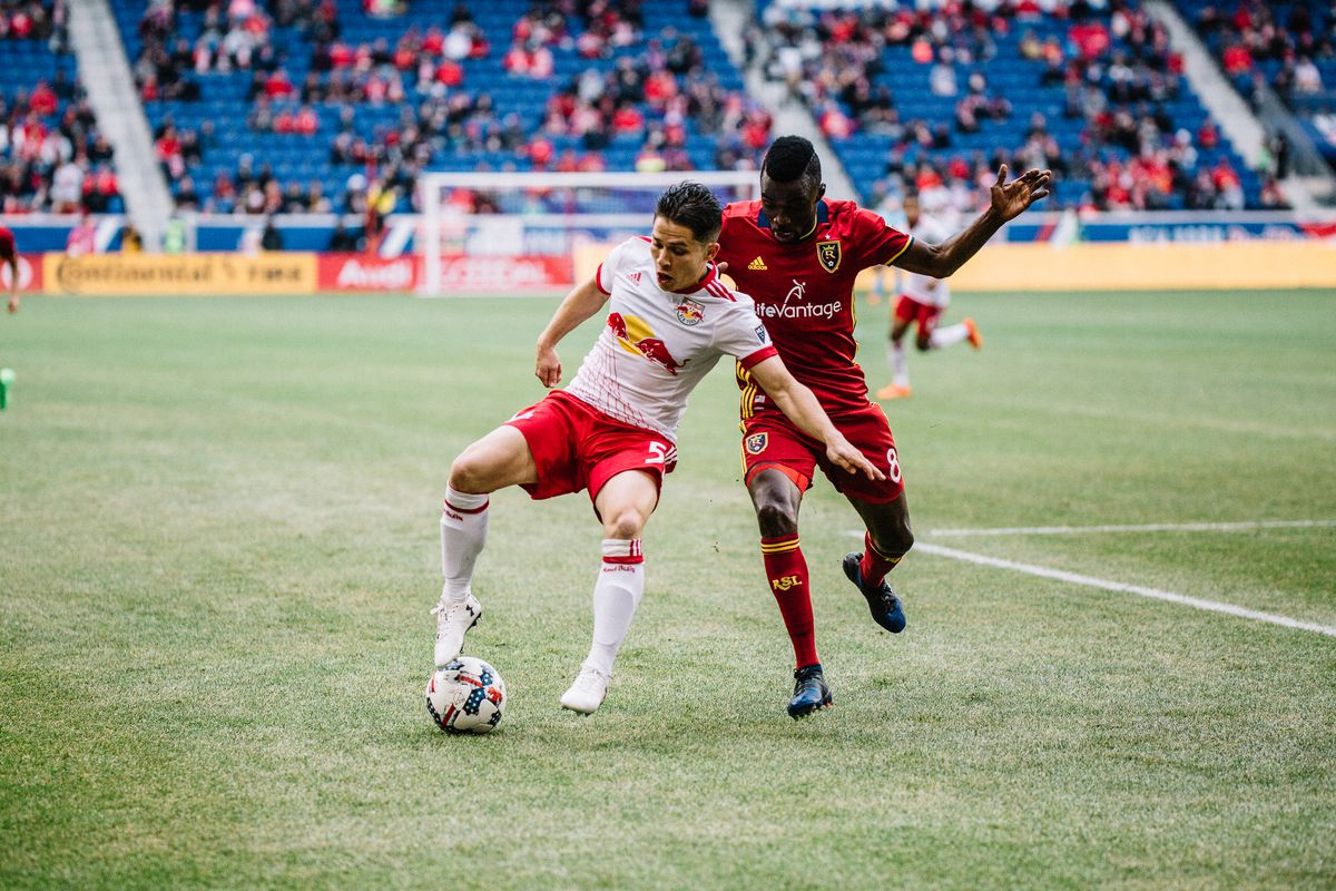 New York Red Bulls defender Connor Lade (5) holds the ball away from Real Salt Lake midfielder Sunny at Red Bull Arena; March 25, 2017