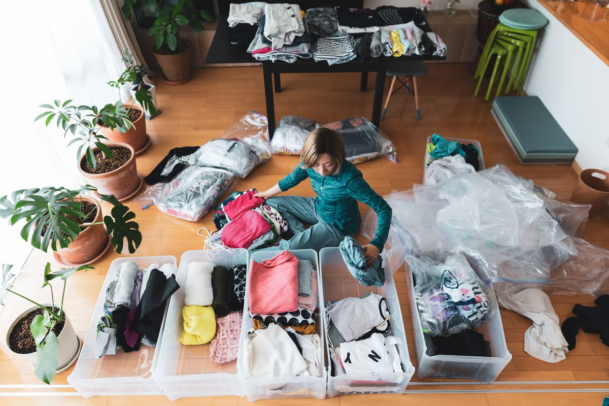 A person sitting on the floor of their house surrounded by organized clutter.