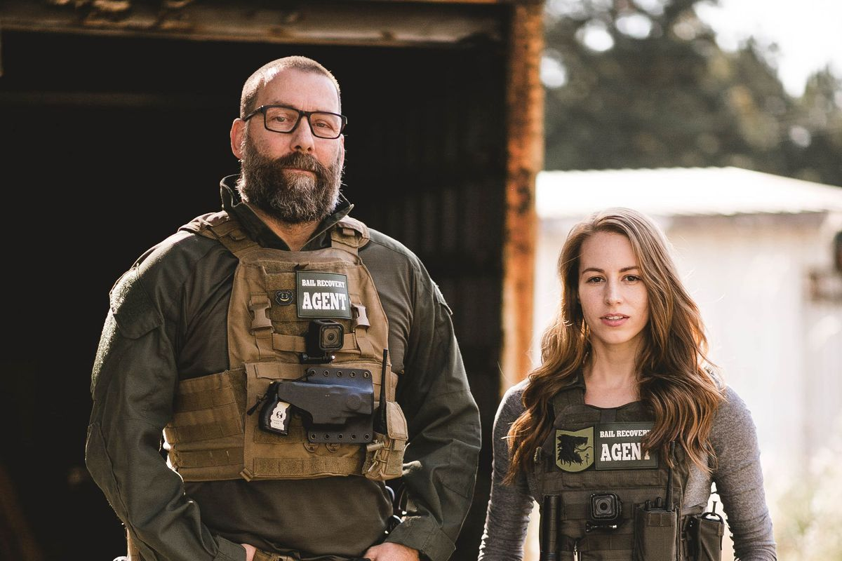 A man and a woman both in protective gear and guns.