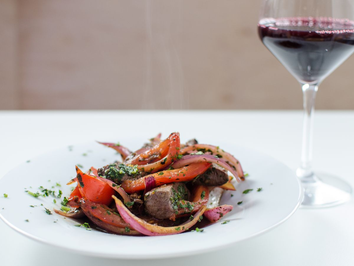 A white plate sits on a white table, full of cubes of marintaed beef with peppers and tomatoes. A glass of red wine sits to the right.