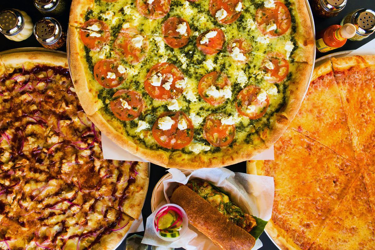 Three pizzas with various toppings are staggered on a table