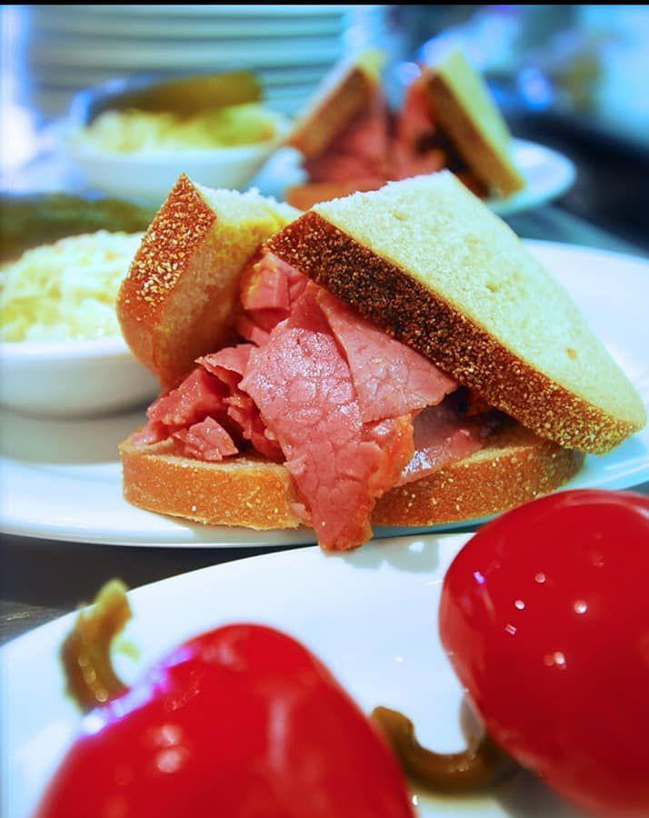 Smoked meat sandwich cut in half on a plate.