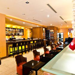 """Everyone knows Rasika Penn Quarter by the crystal strands separating the bar and the dining room, but also the rich plum tones throughout the restaurant. The dining area manages to be both open and capture an intimate feeling. [Photo: <a href=""""http://unde"""