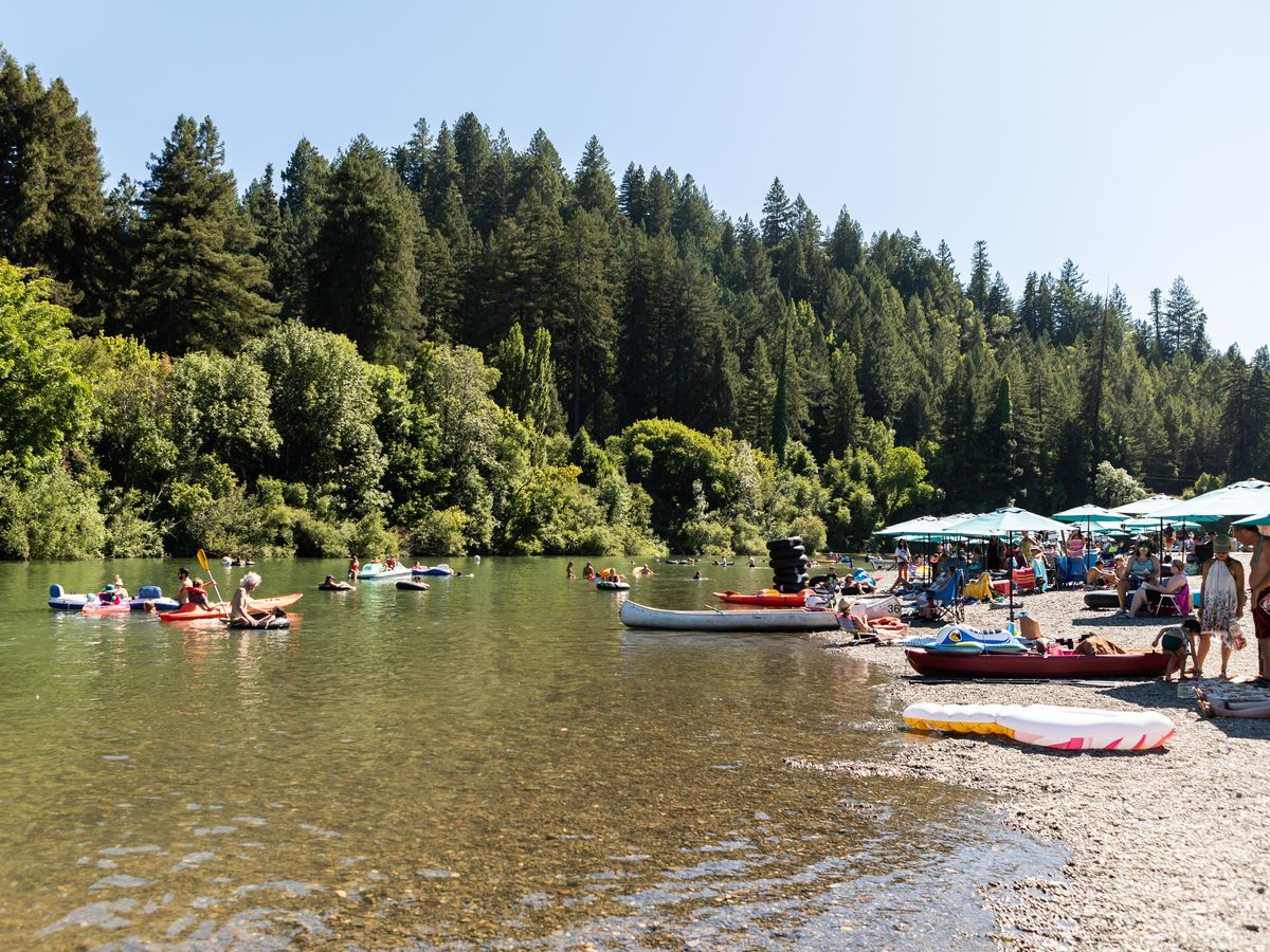 Scene of the Russian River in Guerneville in the sunlight with boats and families on the water.