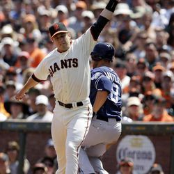San Francisco Giants first baseman Buster Posey can't handle a high throw from third baseman Pablo Sandoval as San Diego Padres' Jason Bartlett reaches the base safely during the fifth  inning of a baseball game in San Francisco,  Sunday, April 29, 2012.