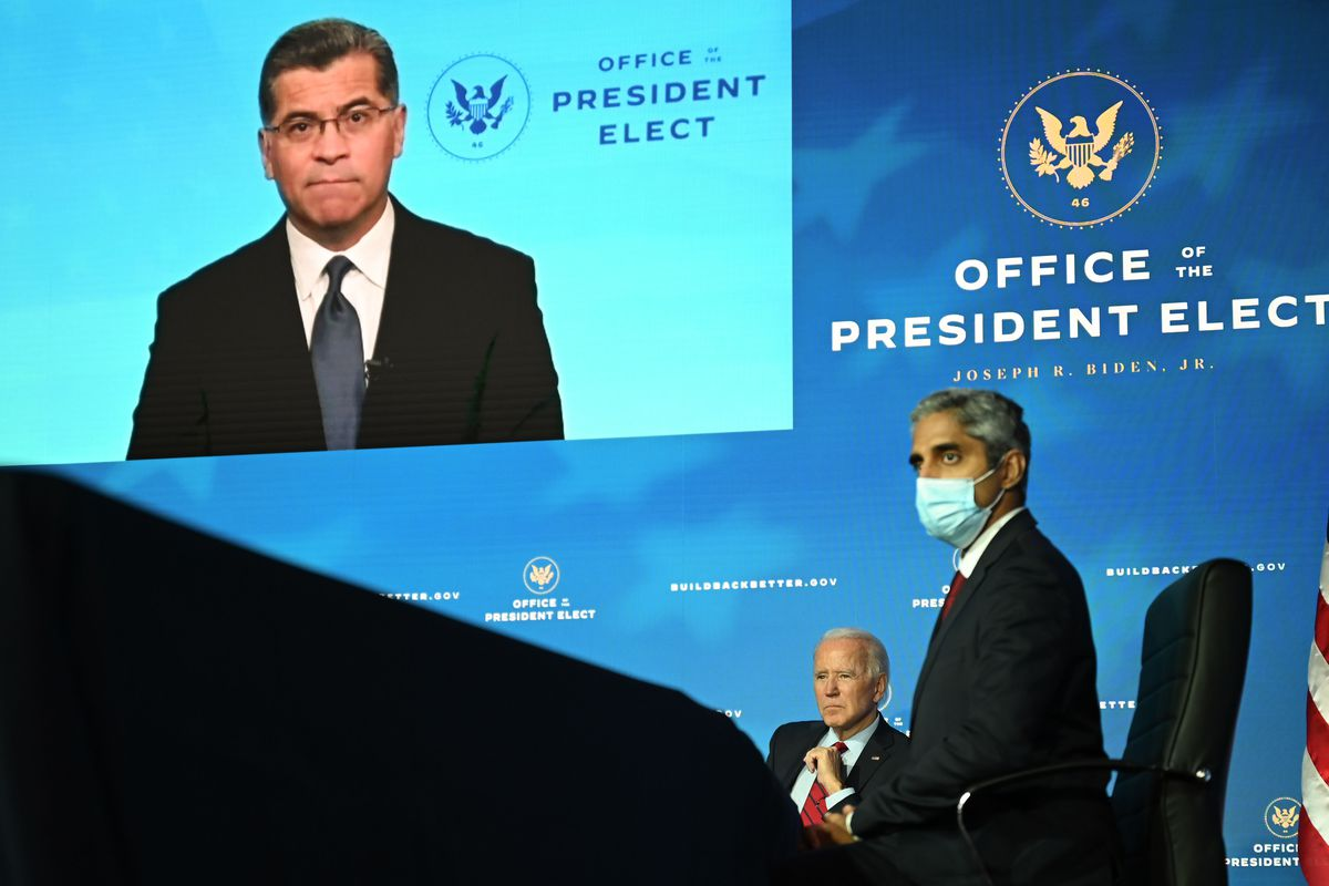 Behind Biden, seated, an image of California Attorney General Xavier Becerra, his HHS pick.