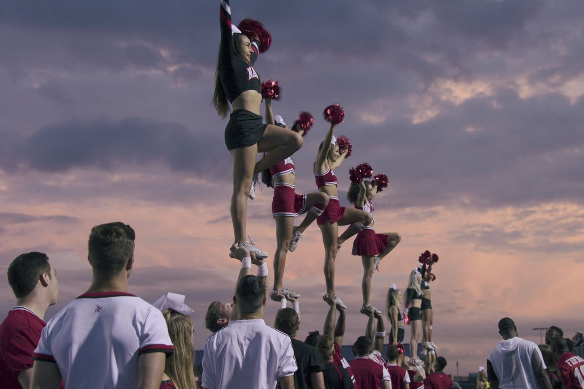 A row of women cheerleaders in red and black uniforms are held precariously aloft by their men counterparts, standing against a purple and orange sunset, in Cheer