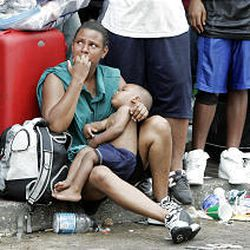 A woman and her child wait with hundreds of other flood survivors Thursday at the Convention Center in New Orleans. Thousands of storm refugees had been assembling outside for days, waiting for help to come.