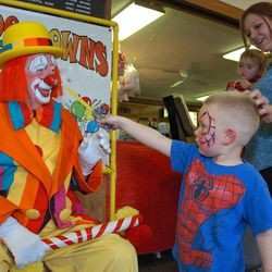 """In this March 29, 2012, photo, Floyd """"Creeky"""" Creekmore visits with a boy at a Shrine circus in Billings, Mont. Guinness World Records has anointed the world's oldest performing clown, and it's none other than Creekmore, a former Montana rancher who's been donning the big nose and bright makeup for almost eight decades."""
