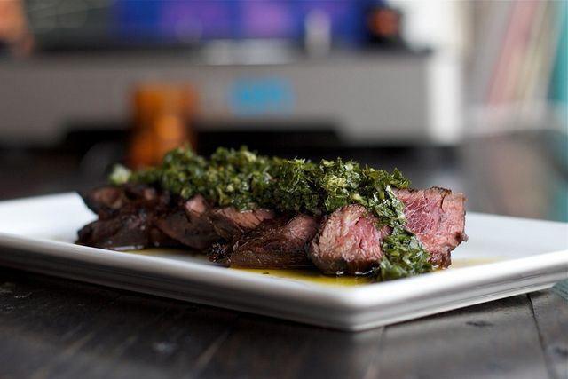 Sliced steak on a platter covered with green chimichurri sauce.
