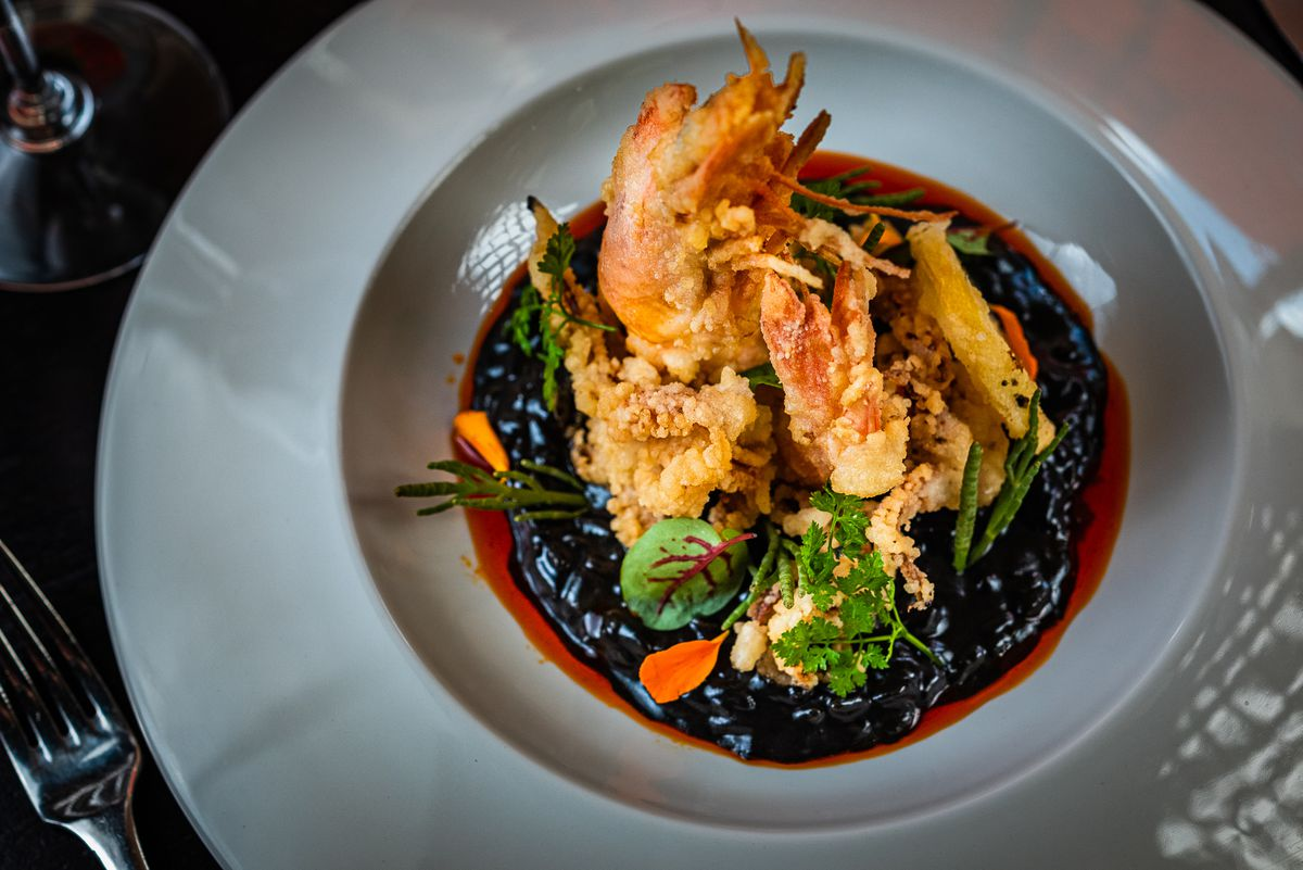A plate of black risotto topped with mixed fried seafood.