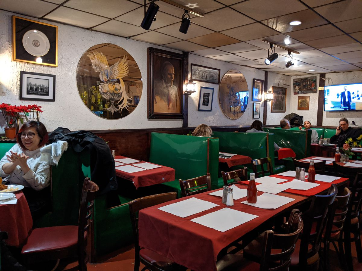A rear dining room has red tablecloths and pictures all over the walls.
