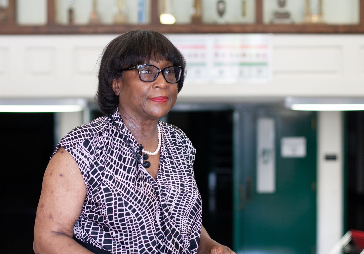 A woman wearing a white and purple shirt, a pearl necklace, black glasses, and multiple television microphones clipped to her collar stands in a high school gym lined with trophies and smiles.