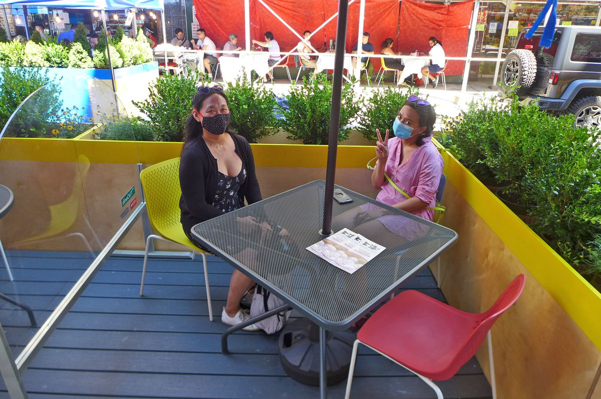 Two women sit at a table in a plexiglass enclosure in the street.