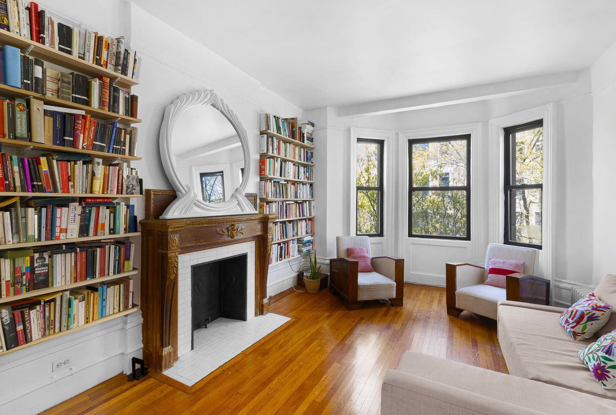A living area with bay windows, a fireplace, several bookshelves, and hardwood floors.