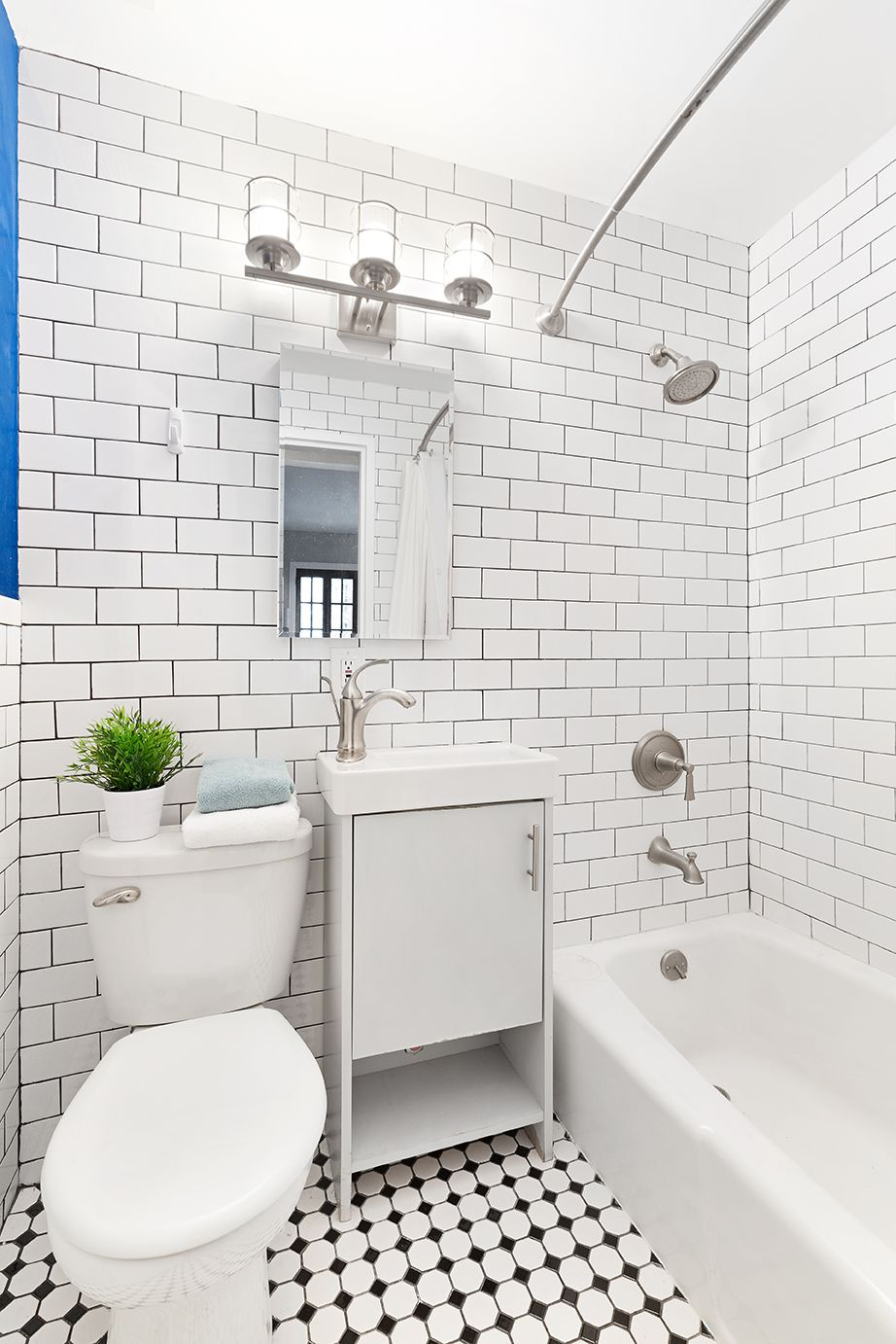 A bathroom with black and white tile floors and white walls.