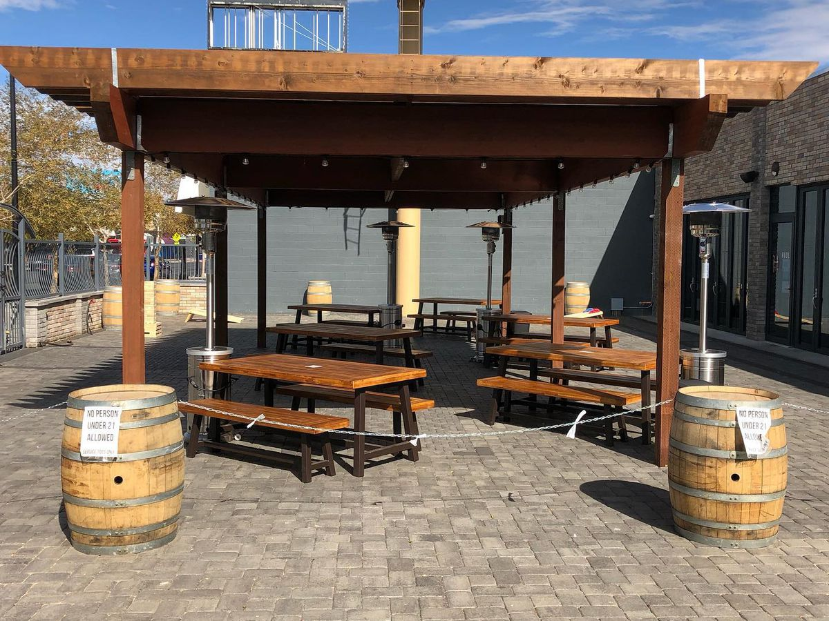 A covered patio with picnic tables and wooden barrels