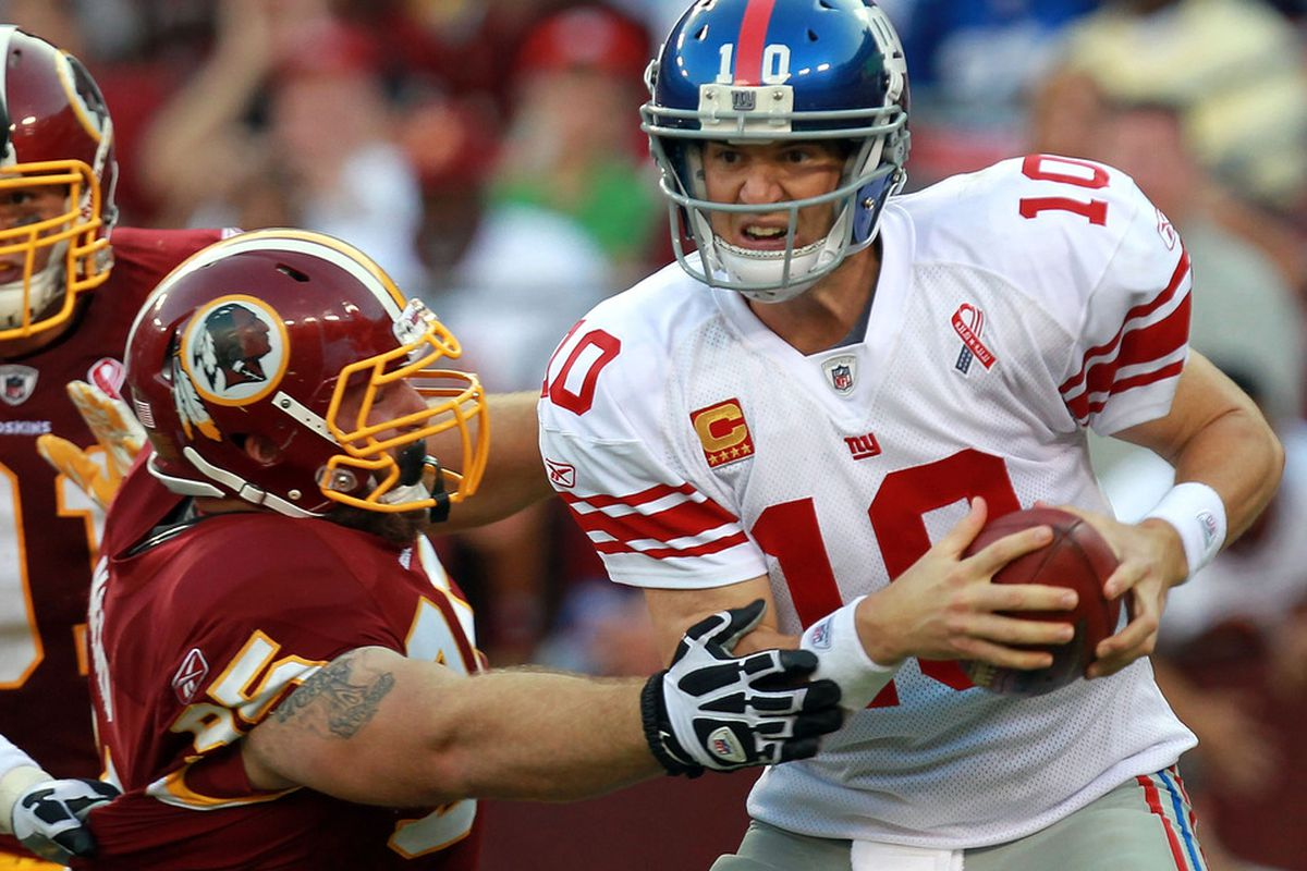 LANDOVER, MD - SEPTEMBER 11:  Eli Manning #10 of the New York Giants is sacked by Chris Neild #95 of the Washington Redskins during the season opener at FedExField on September 11, 2011 in Landover, Maryland.  (Photo by Ronald Martinez/Getty Images)