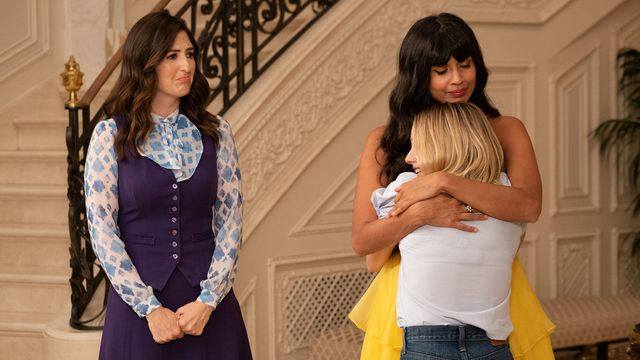 "Eleanor (Kristen Bell) and Tahani (Jameela Jamil) hug as Janet (D'Arcy Carden) looks on sadly in a screenshot from The Good Place season 4, episode 13, ""Whenever You're Ready"""