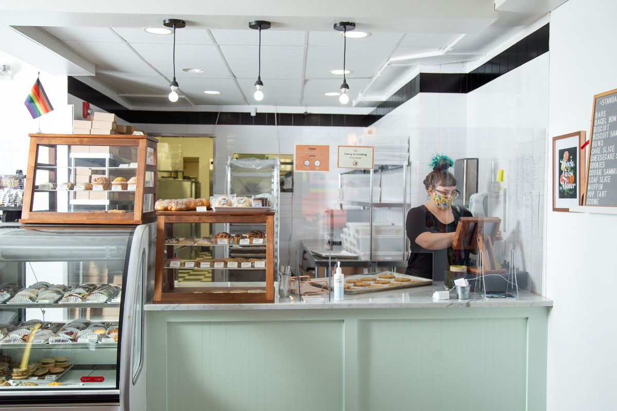 the pastry case and counter at crust vegan bakery with a woman workin behind the counter and baked goods in the case