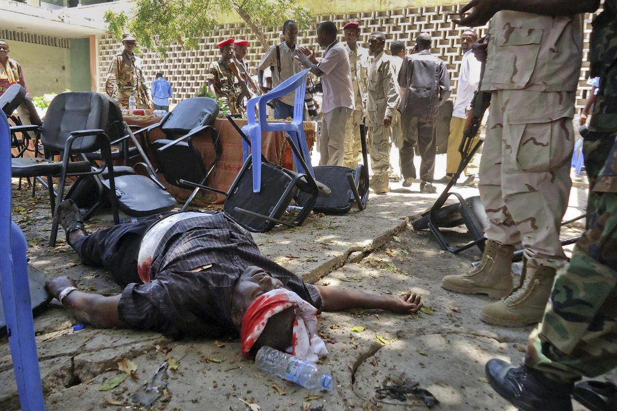 A man wounded in the blast lies on the ground at the Somali National Theater in Mogadishu, Somalia Wednesday, April 4, 2012. An explosion Wednesday at a ceremony at Somalia's national theater killed at least 10 people including two top sports officials in