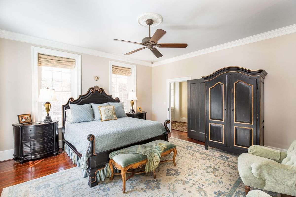 A four poster bed sits in a bedroom with big antique black furniture and a rug.