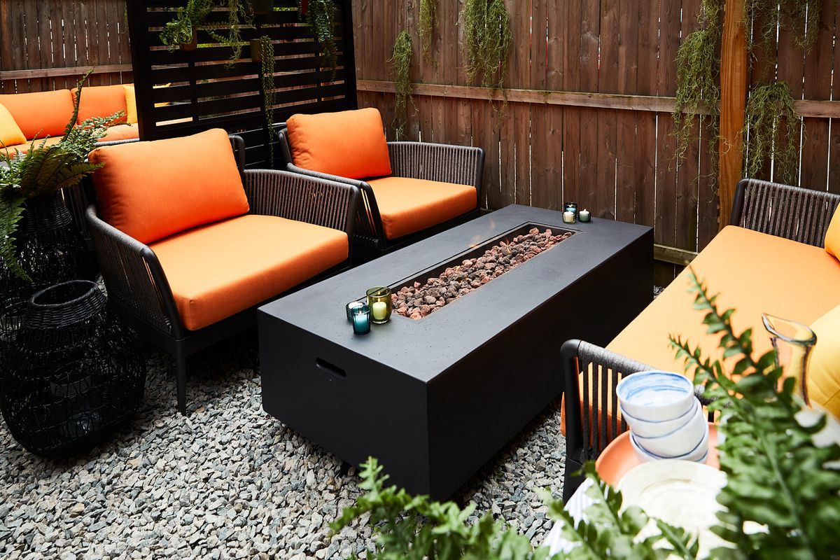 Orange outdoor lounge seating surrounds a fire-pit table. The table is surrounded by dark wood covered with greenery, and the ground is light stone pebbles.