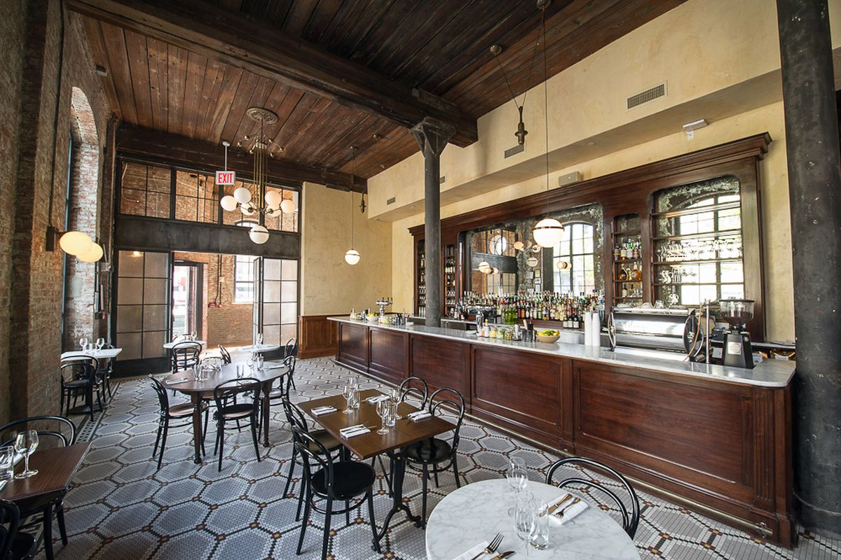 Reynard's bar room has tall ceilings, brown woods, a tile floor, and three tables with bistro-style chairs