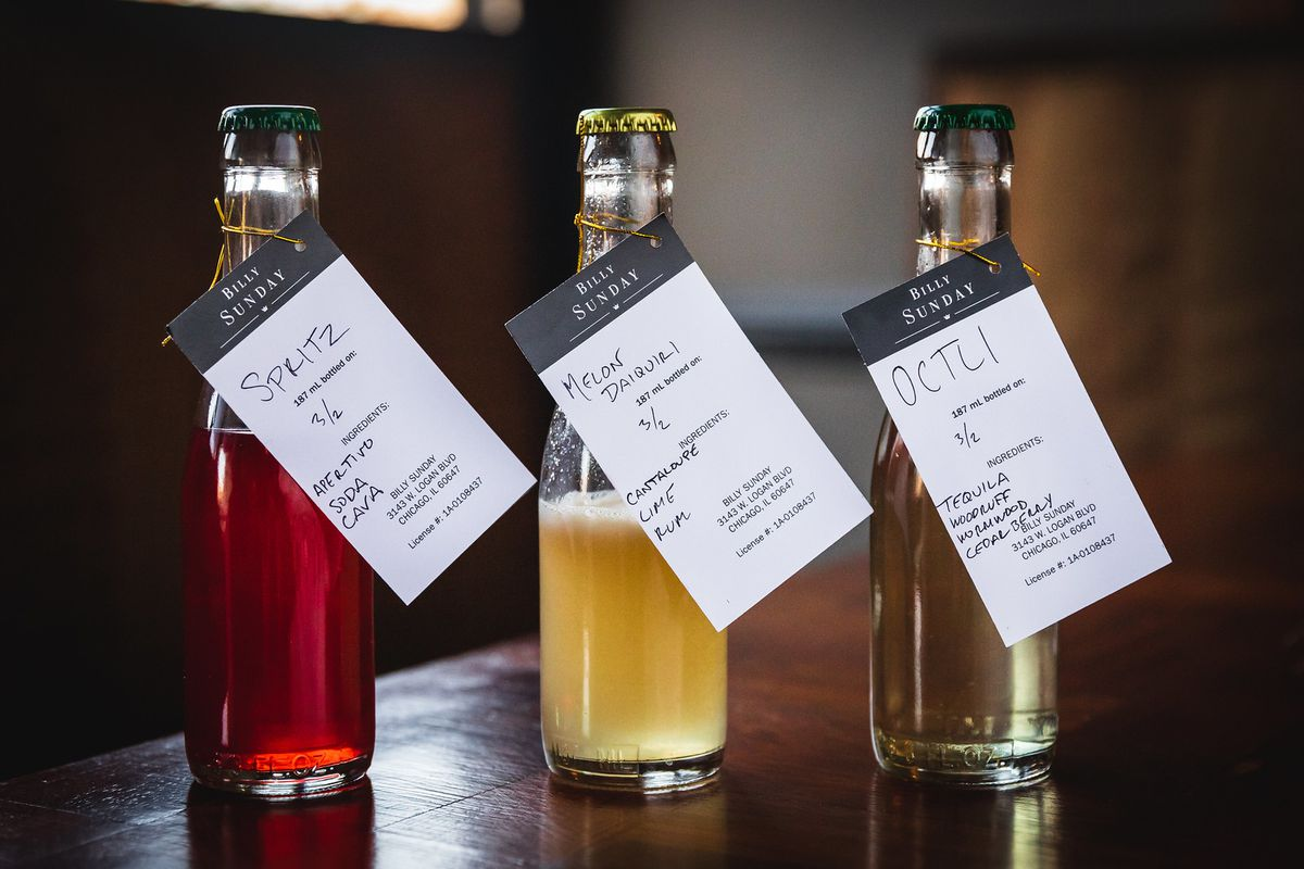 Three bottled cocktails with tags hanging.