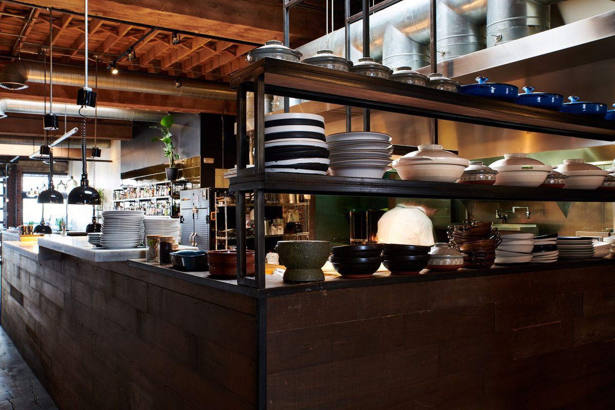 Two shelves of pots and dishes sit next to the kitchen at Bar King. They're generally mismatched, with pots hanging above the hood.