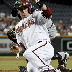 Arizona Diamondbacks' Paul Goldschmidt, front, scores ahead of the tag by San Diego Padres' Yasmani Grandal during the first inning of a baseball game Tuesday, Sept. 18, 2012, in Phoenix.